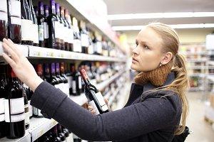 Young woman choosing wine market