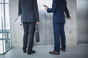 Businessmen standing by lift and pressing button