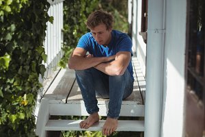 Worried man sitting on porch