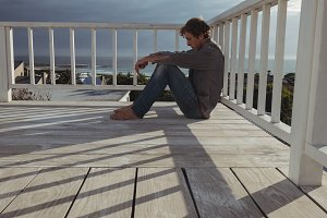 Worried man sitting on balcony