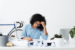 Concentrated young dark-skinned woman wearing glasses and blue shirt sitting at her workplace holding pen writing in papers working at her sketches holding her hand on head being tired of work