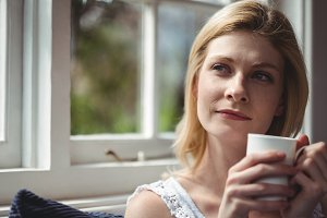 Thoughtful woman having coffee in living room