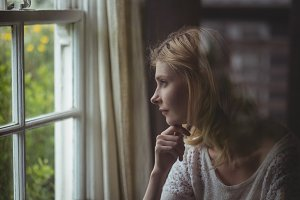 Beautiful woman looking through window