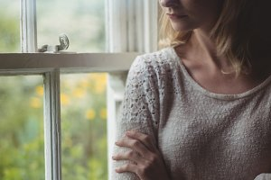 Thoughtful woman standing at window