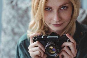 Beautiful woman holding digital camera