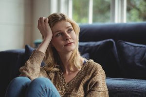 Thoughtful woman sitting in living room