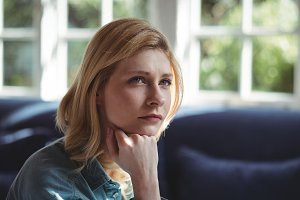 Close-up of thoughtful woman in living room