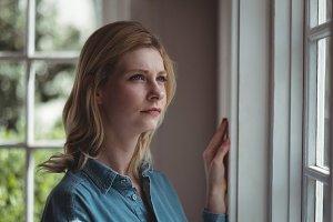 Thoughtful woman looking through window