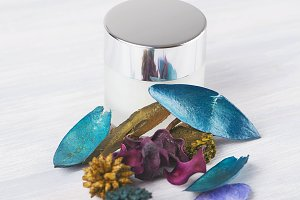 Can of cream for the skin next to the decorative flowers of several colors on the wooden table. Cosmetics.