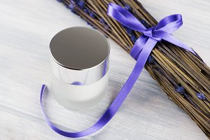 Close-up of a can of cream for the skin next to lavender flower on white wooden table. Cosmetics.