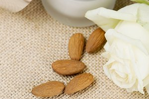 Close-up of a pot of skin cream next to almonds and a white rose on brown rustic fabric. Vertical shoot.
