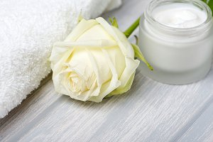 Close-up of cream jar for skin and white rose on wooden table. Cosmetics. Horizontal shoot.