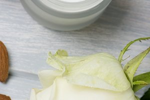 Close-up of a pot of cream for the skin, white rose and almonds on wooden table. Vertical shoot.