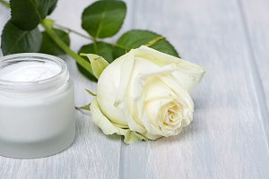 Bottle of cream for skin and white rose on wooden table. Cosmetics.