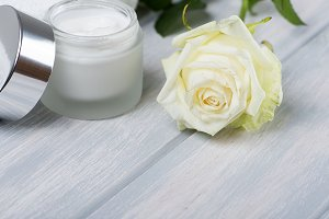 Bottle of cream for the skin, towel and white rose on wooden table. Flower. Horizontal shoot.