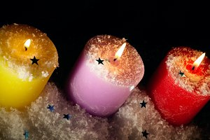 Three candles with artificial snow.