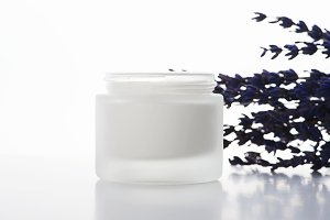 Close-up of lavender flowers and pot of cream for skin on white background. Isolated.