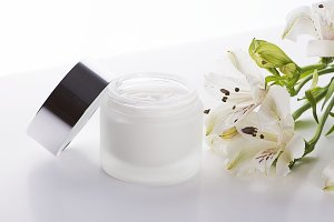 Close-up of bottle of skin creamNext to the lid and lily flowers on white background. Isolated.