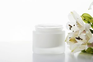 Close-up of bottle of skin creamNext to lily flowers on white background. Isolated.