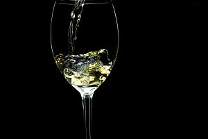Wine pouring into a glass on a black background