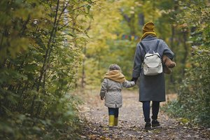 Young mother and her daughter little girl moving away in a autumn park