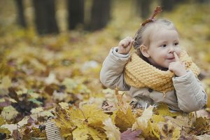 Little blonde girl plays with yellow leaves in autumn park