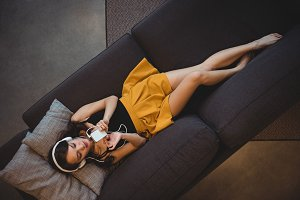 Woman lying on sofa while listening to music with mobile phone