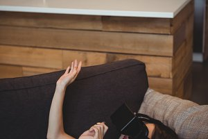 Woman using virtual reality headset while lying on sofa in living room