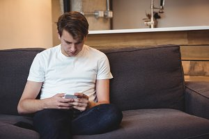 Man sitting on sofa using mobile phone in living room
