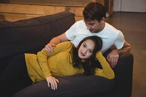 Cheerful couple lying together on sofa in living room