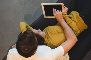 Cheerful couple lying together on sofa using digital tablet