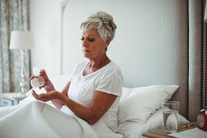 Senior woman taking medicine in bedroom