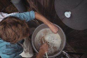Man testing temperature of beer in wort while making beer