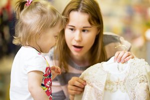A young mother chooses a dress for her little daughter