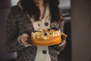 Mid section of woman holding blueberry cake in living room