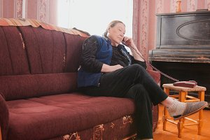 Elderly woman talking on the phone in the apartment
