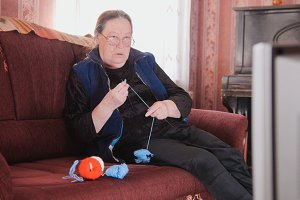 An elderly woman is knitting some socks and watching TV