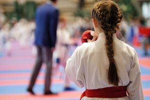 Karate girl in a white kimono with red belt ready to fight