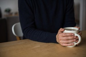 Man holding a cup of black coffee at home
