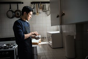 Man using pestle and mortar in kitchen