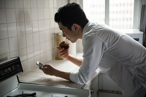 Man using mobilephone while having a cupcake at home