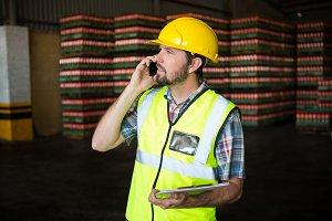 Male worker talking on phone in factory