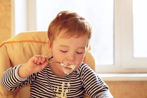 Two year old boy eats porridge