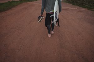 Man carrying surfboard and shoes walking on road