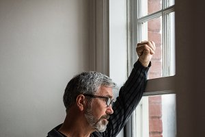 Thoughtful man looking through window