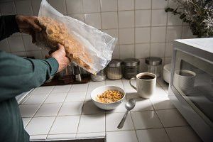 Man pouring cereals in bowl at home
