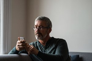 Man using mobile phone in living room