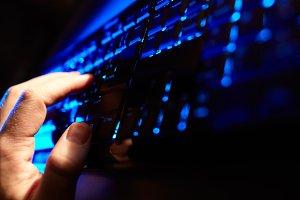 Man's hand typing blue keyboard.