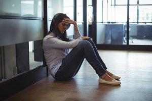 Upset businesswoman sitting on floor