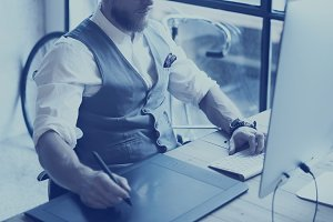 Closeup view of bearded creative manager drawing with digital tablet.Stylish young man wearing white shirt,waistcoat and working at the desktop computer in modern loft.Horizontal,film effect,blurred.